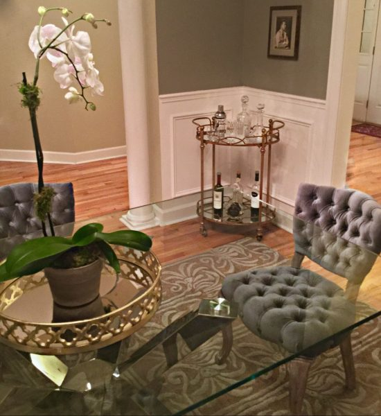 Glass dining table with gray tufted chairs and a gold two tired bar cart.