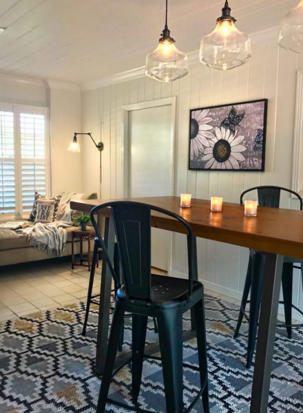 Showing three forms of lighting. Three overhead pendants hang from the ceiling, wall sconce on the wall is over the daybed, and there are three lit candles on the table.