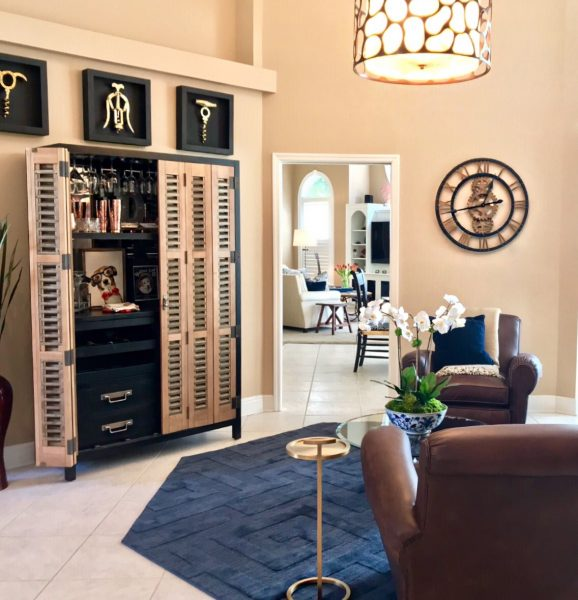 Room has a libation lock, navy blue rug, two brown leather club chairs, large industrial clock on the wall, and framed brass cork screws on the wall for this hip chill lounge.