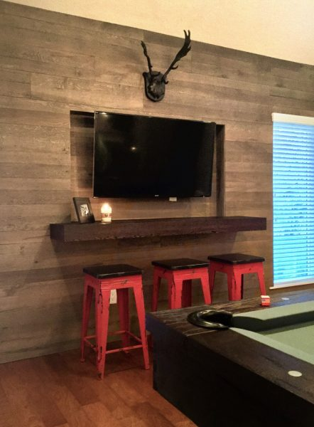 Beverage bar has red industrial style counter stools, a large flat screen TV, and deer mount.