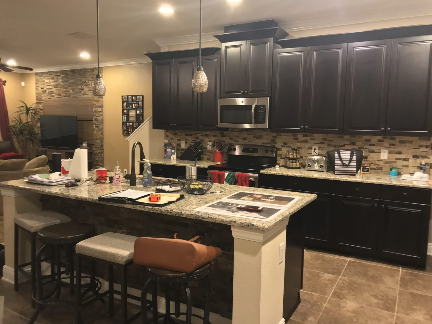 Cluttered kitchen with small appliances, dish soap, spices, stacks of papers, paper towels etc. all over the counter tops.