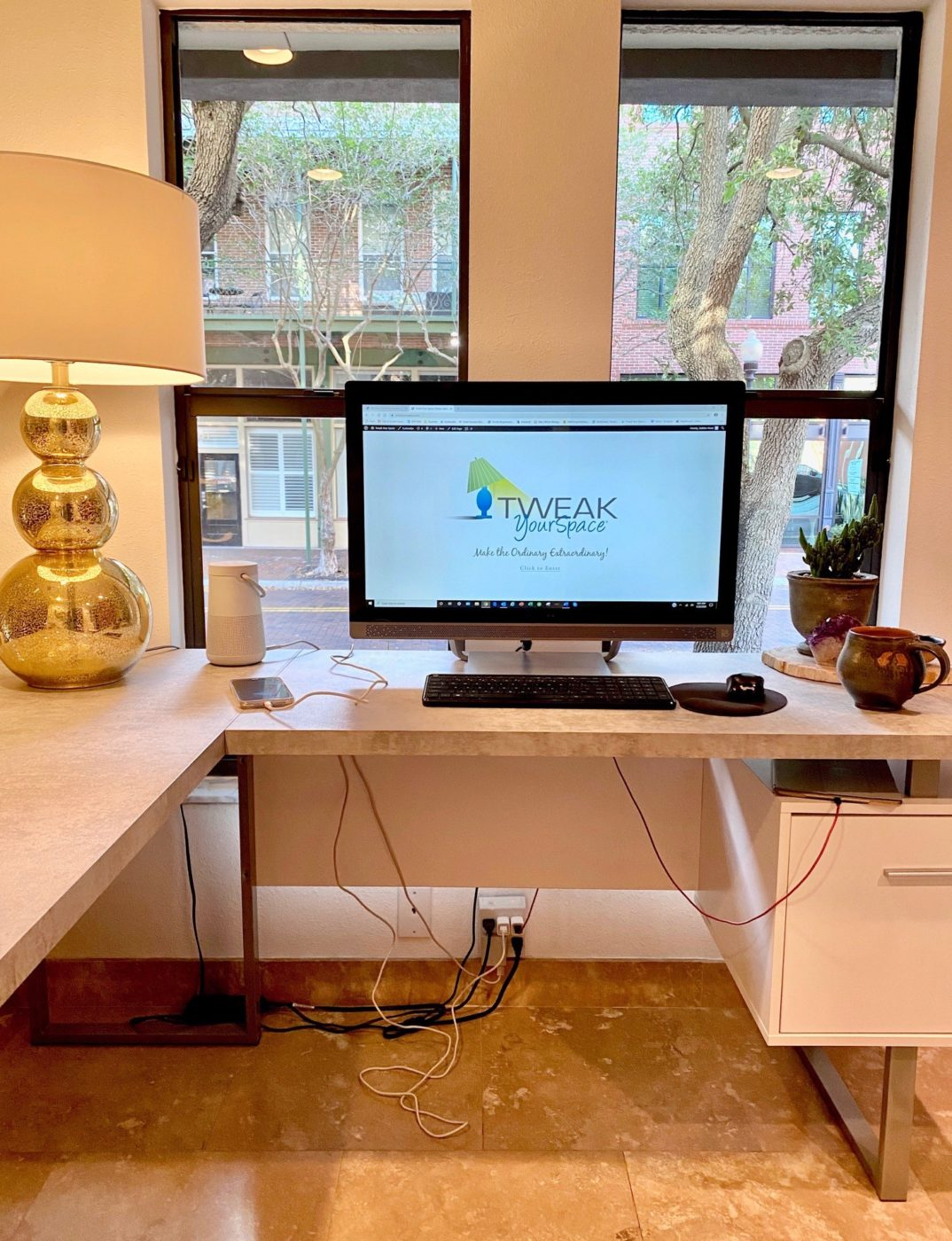 Tweak Your Space office showing a desk with cords running under and over the desk. Cord clutter doesn't make us happy.
