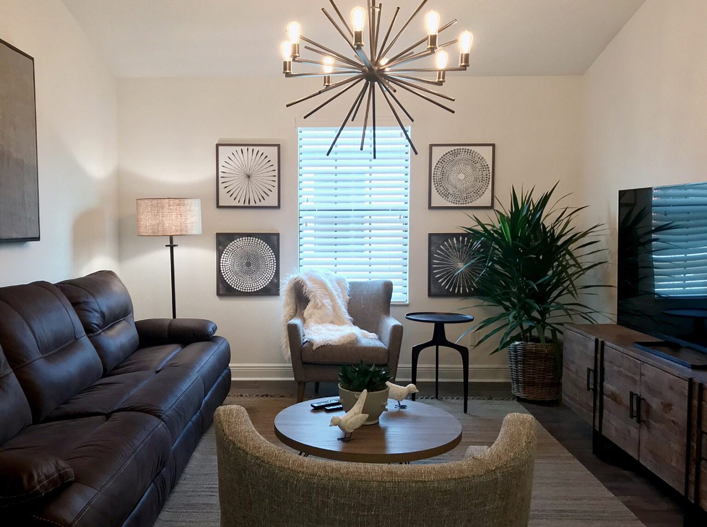 A light and bright happy space with the blinds open, white walls, and stunning overhead light fixture.