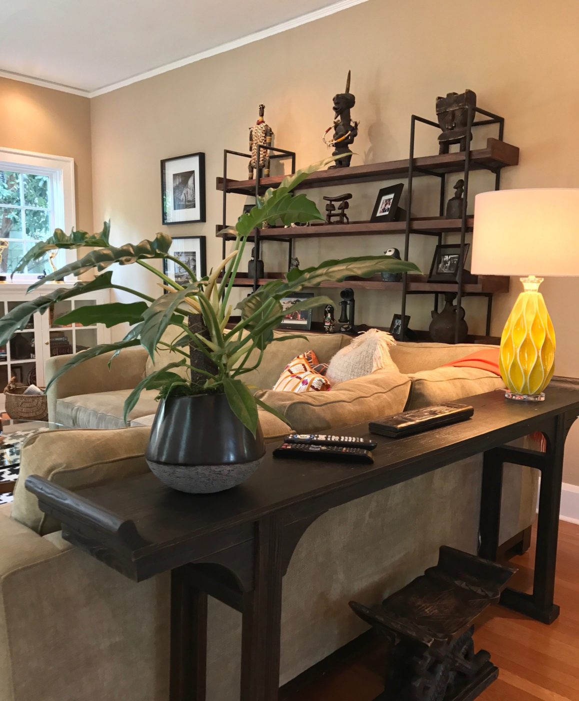Picture is showing the back of the sofa with a console table with a yellow mid-century modern lamp and potted plant. Over the top of the sofa you can see the new display shelves showcasing the homeowners African art collection.