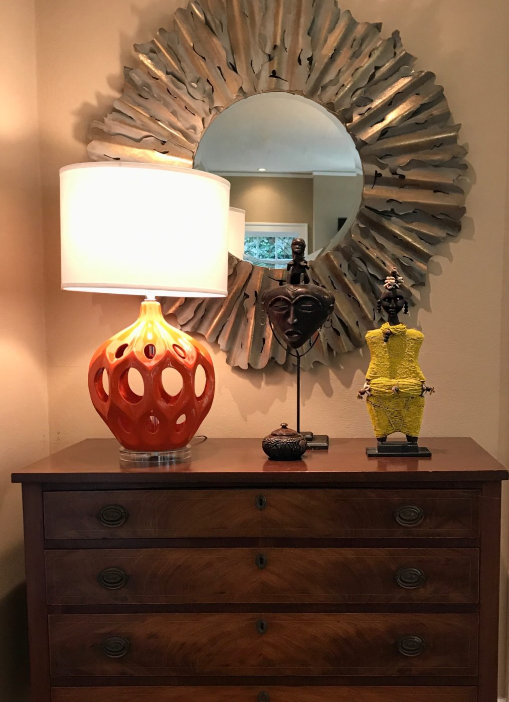 Antique chest used to display homeowners collection of African sculptures coupled with a round mirror and lamp.