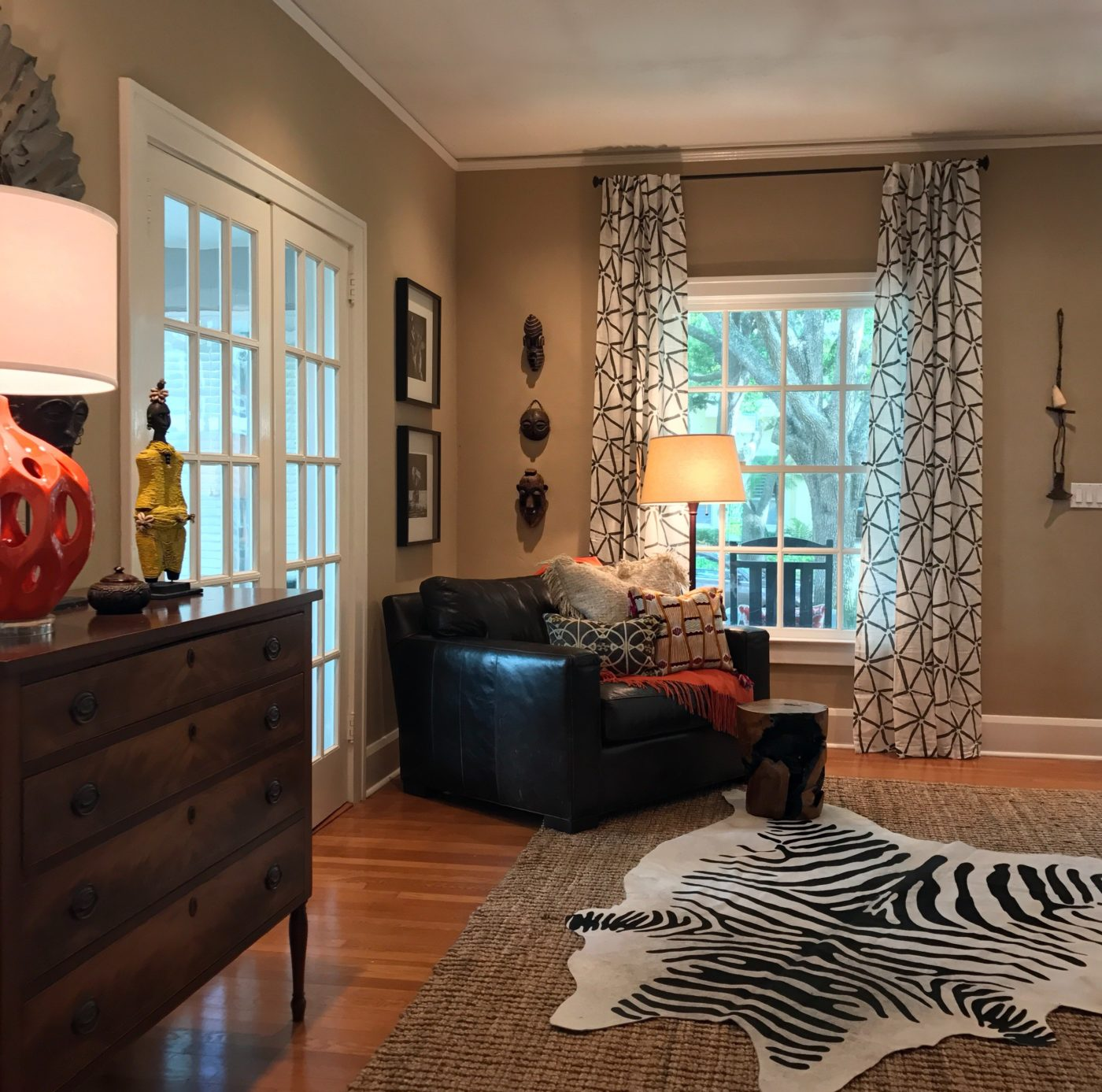 Cozy reading corner with layered rugs on the floor, ethnic patterned drapes and and the homeowners African mask collection displayed vertically on the wall.